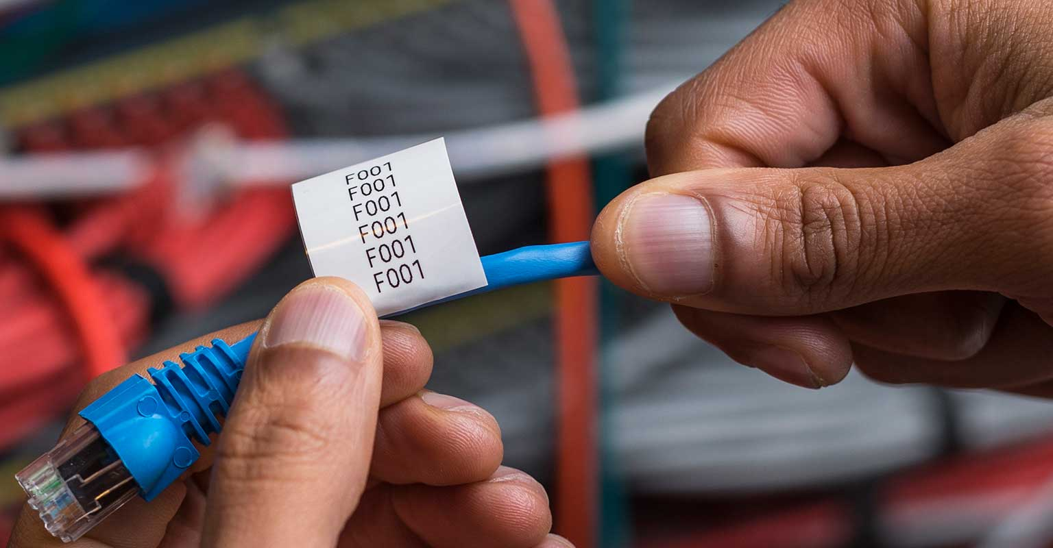 Brother TZe cable label being prepared for wrapping around network cable