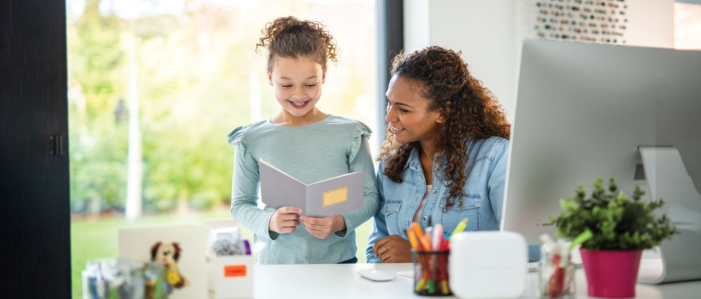 A woman and her little girl are at home laughing together while looking through a home schooling workbook created with Brother's Creative Center.