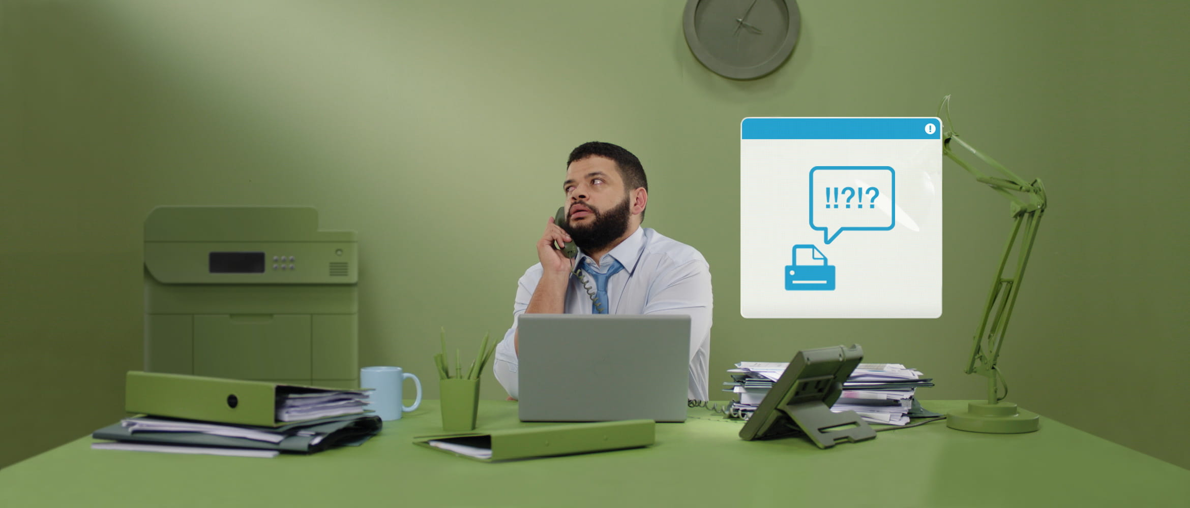 Man in office sat at desk on the phone