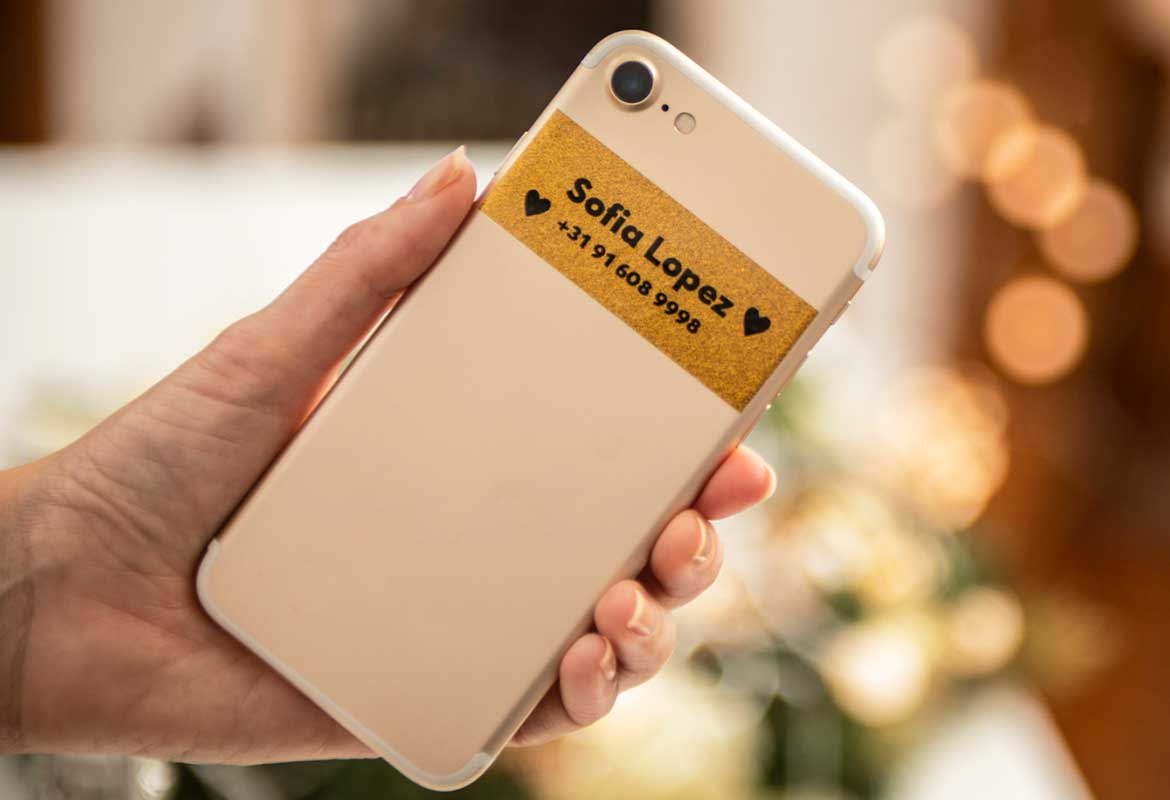 Black on premium gold glitter label on smartphone with owner's name and contact number