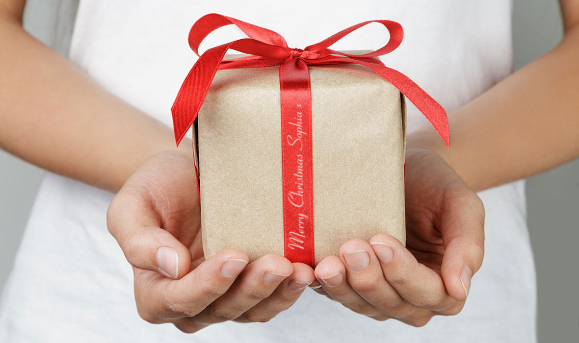 Christmas present, neatly wrapped in a red ribbon with a personalised message printed on the ribbon
