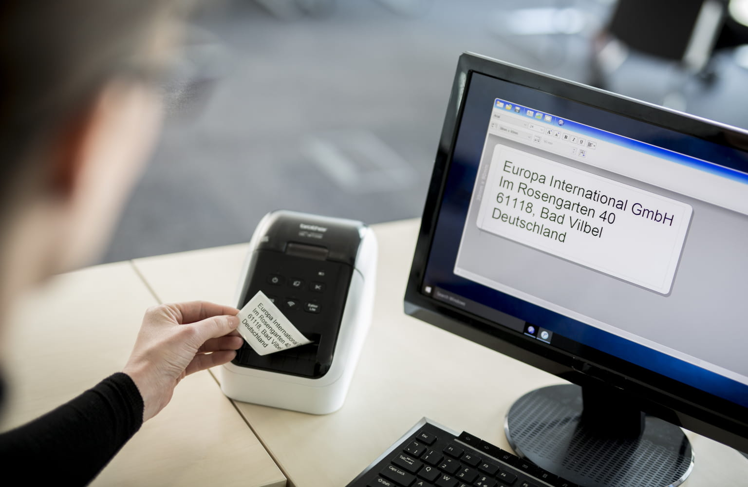An office worker removes a printed label from their QL label printer