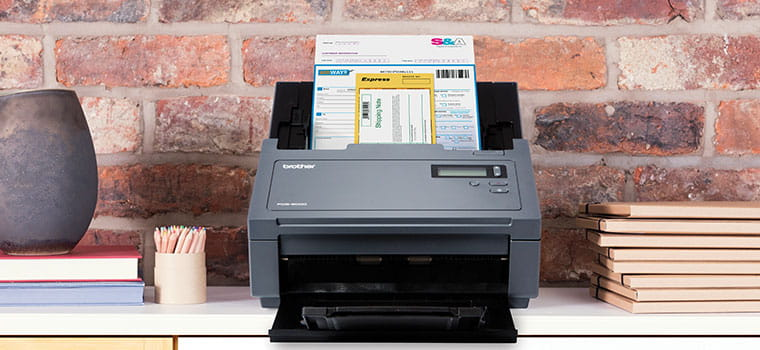 Brother PDS-6000 professional scanner scanning a document, brick wall, vase, note books