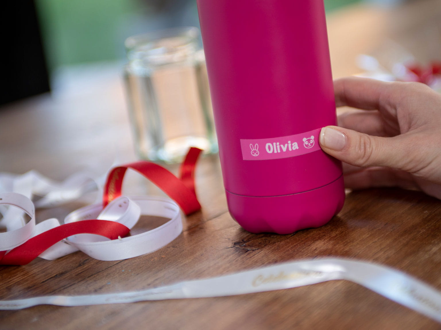 Brother pink label on pink water bottle with white and red ribbons