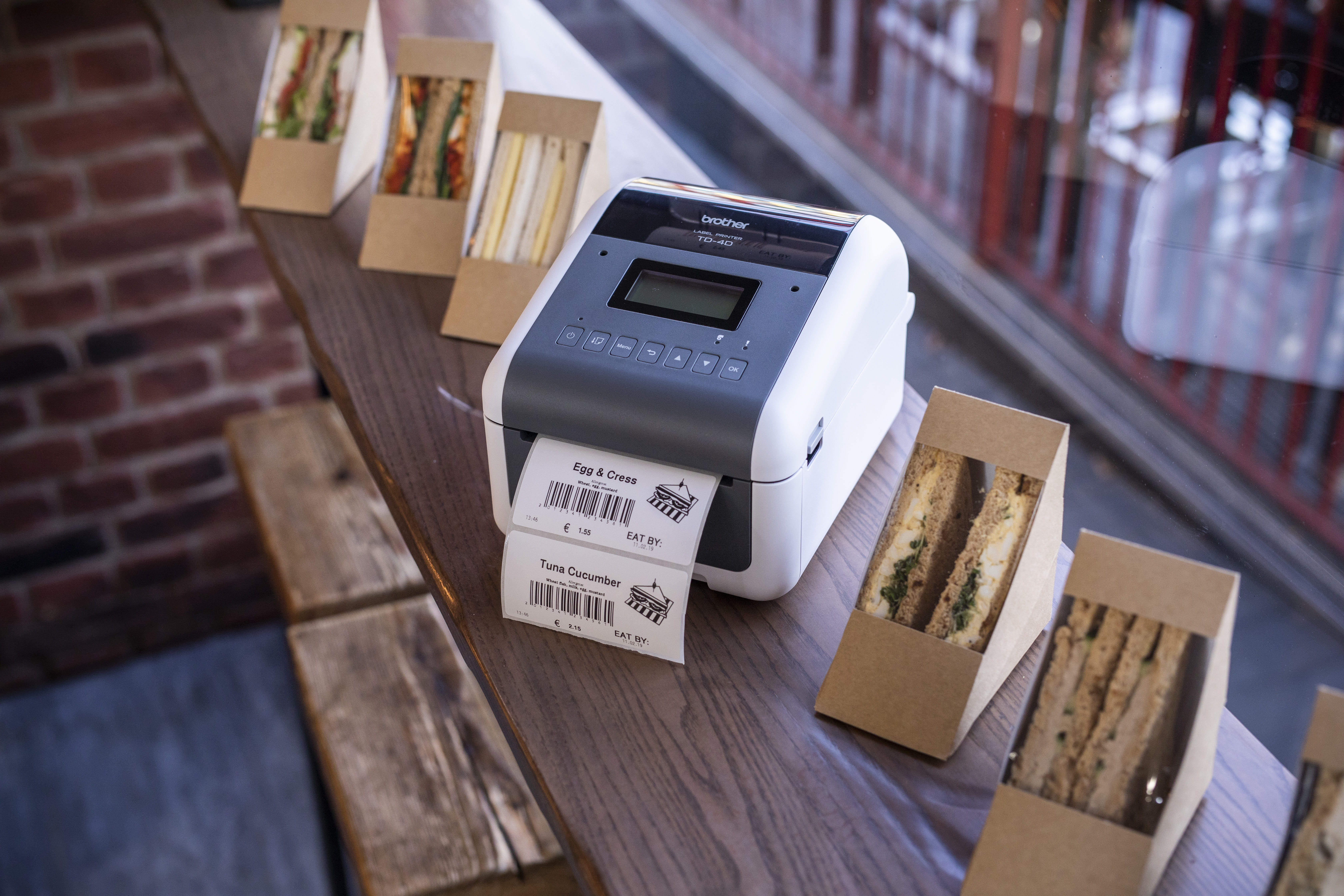 TD-4D labelling machine printing a label to stick on sandwich boxes in a deli retail area