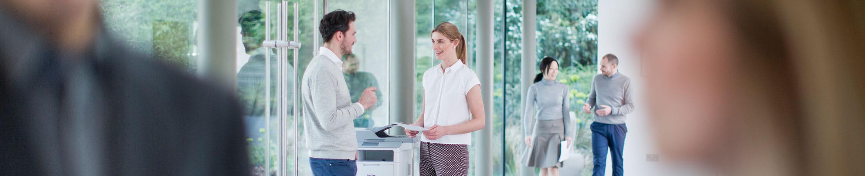 Man and woman talking next to a printer