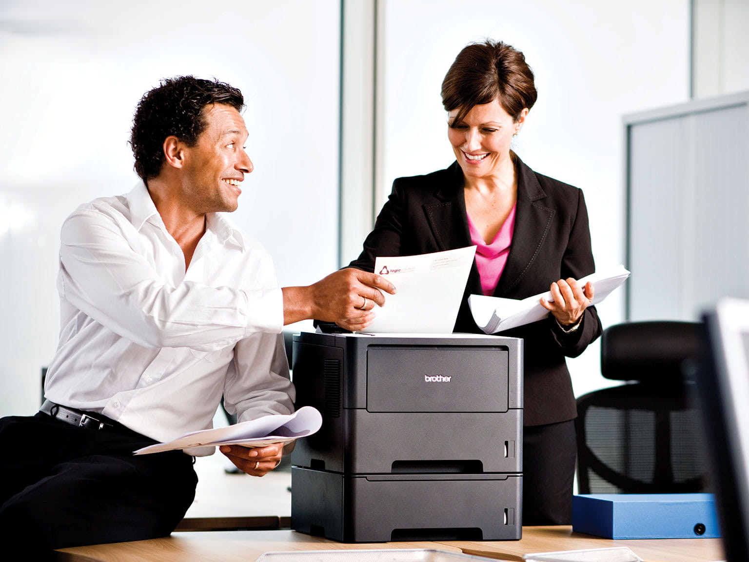 Coworkers smiling over a Brother printer