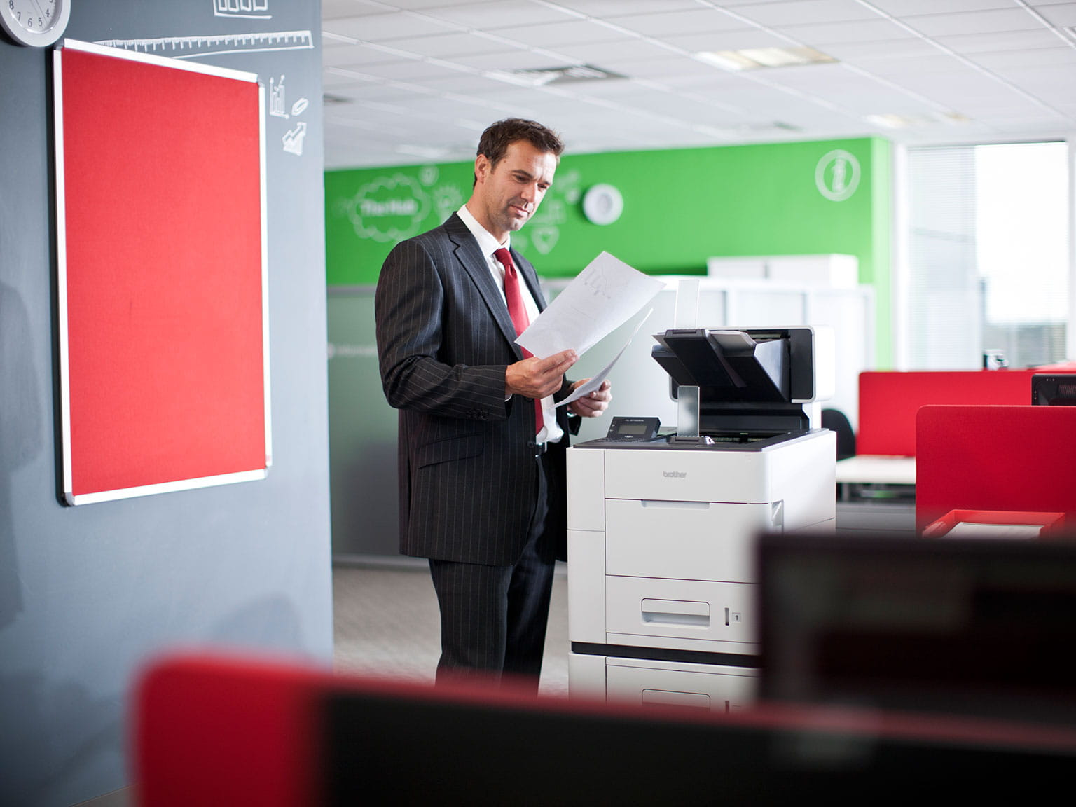 Businessman holding papers in front of a Brother computer